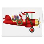 Papá Noel en el biplano con las tarjetas de felici