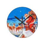 Papá Noel para arriba en el tejado en la nieve Relojes De Pared