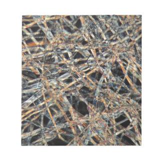 Papel de la bolsita de té debajo del microscopio blocs