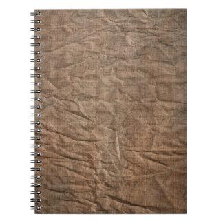 Papel marrón arrugado con el cuaderno de la