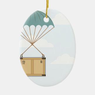Paracaídas con un paquete adorno navideño ovalado de cerámica