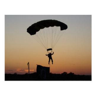 Paracaídas del Skydiver en la postal de la puesta
