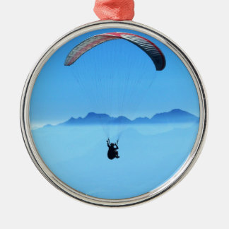 Paraglider on blue background with mountains round metal christmas ornament