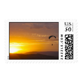 Paragliding on the sunset postage