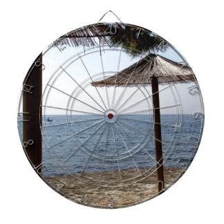 Paraguas de la paja en la playa tabla dardos
