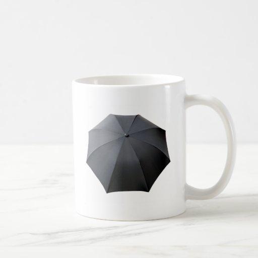 Paraguas negro aislado sobre el fondo blanco tazas