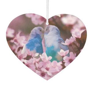 Parakeets cariñosos y flores rosadas