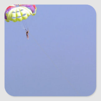 Parasailing over the blue water square sticker