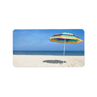 Parasol de playa colorido en la playa de Sandy Etiqueta De Dirección