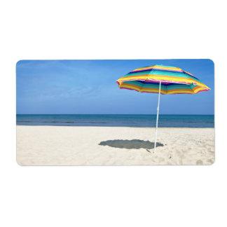 Parasol de playa colorido en la playa de Sandy Etiquetas De Envío