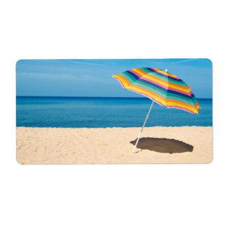 Parasol de playa en un día soleado, mar en fondo etiqueta de envío