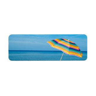 Parasol de playa en un día soleado, mar en fondo etiqueta de remite