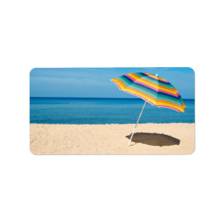 Parasol de playa en un día soleado, mar en fondo etiquetas de dirección