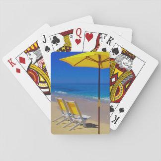 Parasol de playa y sillas amarillos en prístino barajas de cartas