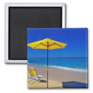 Parasol de playa y sillas amarillos en prístino iman para frigorífico