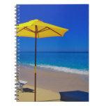 Parasol de playa y sillas amarillos en prístino libros de apuntes