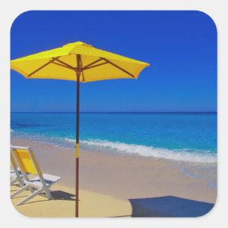 Parasol de playa y sillas amarillos en prístino pegatina cuadrada