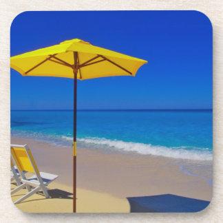 Parasol de playa y sillas amarillos en prístino posavasos de bebidas