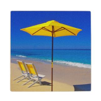 Parasol de playa y sillas amarillos en prístino posavasos de madera