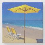 Parasol de playa y sillas amarillos en prístino posavasos de piedra