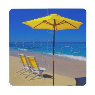 Parasol de playa y sillas amarillos en prístino posavasos de puzzle