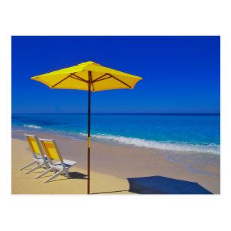 Parasol de playa y sillas amarillos en prístino postal