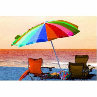 Parasol de playa y sillas invertidos coloridos en esculturas fotográficas