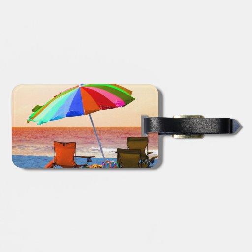 Parasol de playa y sillas invertidos coloridos en  etiquetas maleta