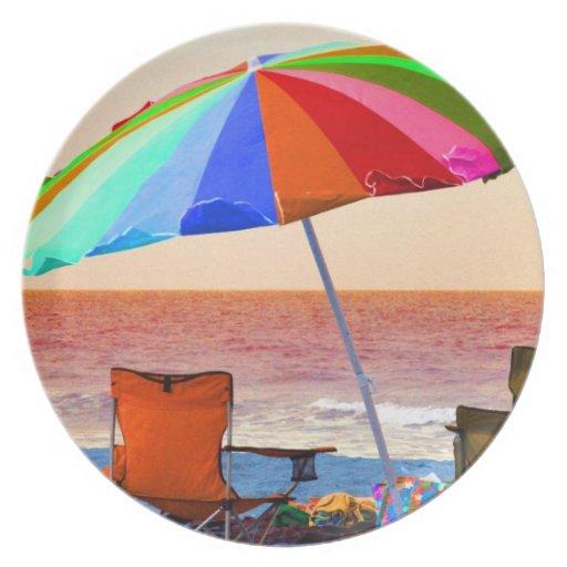 Parasol de playa y sillas invertidos coloridos en  platos de comidas