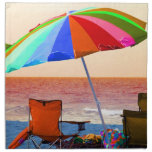 Parasol de playa y sillas invertidos coloridos en  servilletas de papel