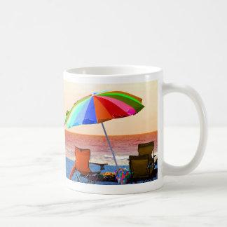 Parasol de playa y sillas invertidos coloridos en  taza básica blanca