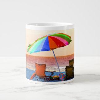 Parasol de playa y sillas invertidos coloridos en taza de café grande