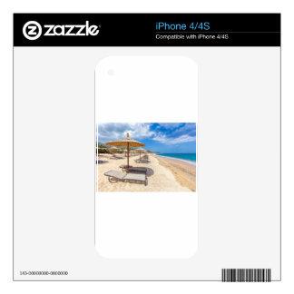 Parasoles de playa en filas en la playa arenosa skins para iPhone 4S