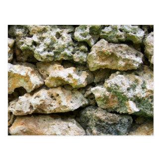 Pared áspera de la roca con el fondo del personali postal