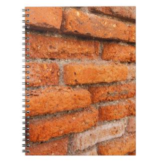 Pared de ladrillo anaranjada rubicunda libros de apuntes con espiral