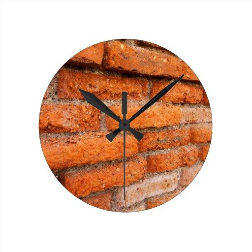 Pared de ladrillo anaranjada rubicunda relojes