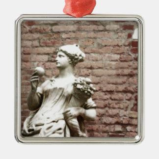 Pared de ladrillo y estatua de la mujer adorno navideño cuadrado de metal