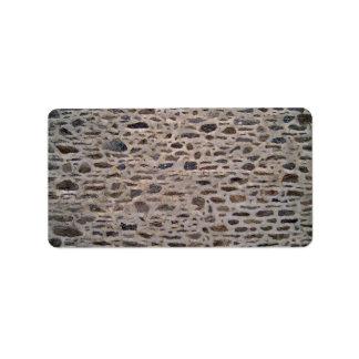 Pared de piedra con el modelo irregular etiquetas de dirección
