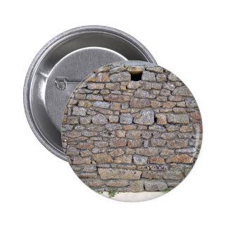 Pared de piedra con el solo agujero y las pequeñas pins