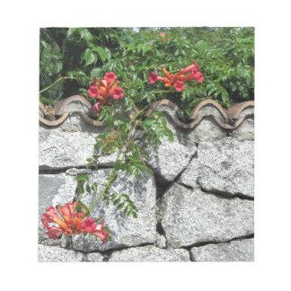 Pared de piedra decorativa con las flores blocs de papel