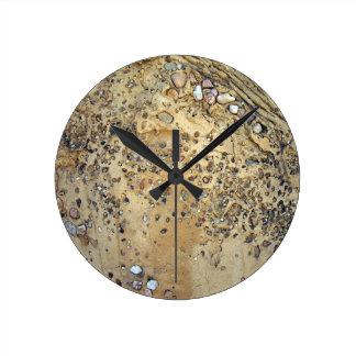 Pared del cemento entremezclada con las piedras reloj redondo mediano