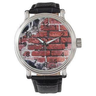 pared urbana del ladrillo rojo con la pintada reloj de mano