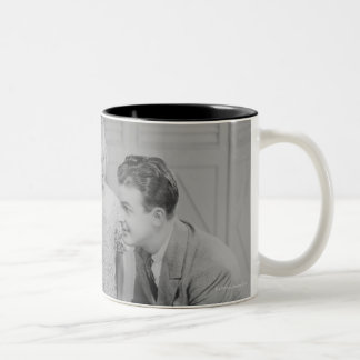 Parents and daughter (6-7) talking with male Two-Tone coffee mug