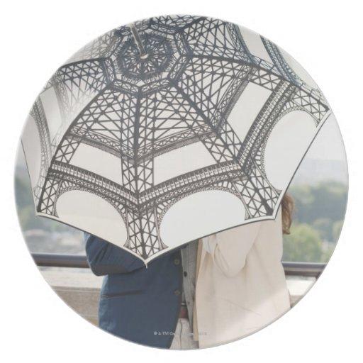 Pares debajo de un paraguas con la torre Eiffel Platos