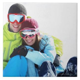 Pares del Snowboarder que se sientan en nieve Azulejo Cuadrado Grande