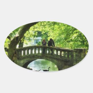 Pares en el puente en parque calcomanías óvales