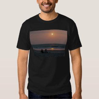 Pares en la playa en la puesta del sol polera