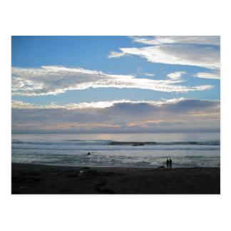 Pares en la playa que mira en puesta del sol y el  postales