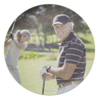 Pares maduros que juegan a golf plato de comida