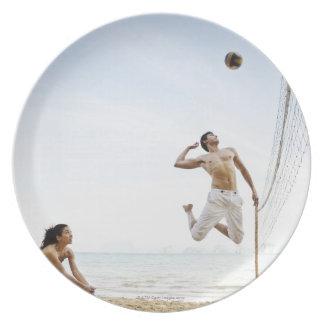 Pares que juegan a voleibol de playa en seis plato de comida